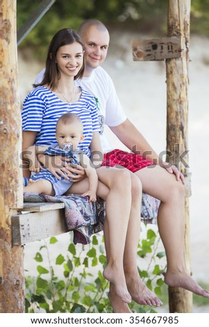Happy smiling family of slim fit beautiful brunette mother, bold fat father and cute little infant baby on a seashore near nature in blue, white and red outfit: t-shirt and shorts. Summer - stock photo