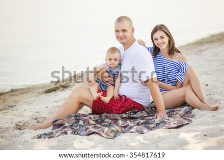 Happy smiling family of slim fit beautiful brunette mother, bold fat father and cute little infant baby on a seashore near water in blue, white and red outfit: t-shirt and shorts. Summer. Copy space - stock photo