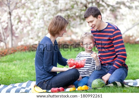 happy smiling family of three having a picnic outside together, eating watermelon and having fun together - stock photo