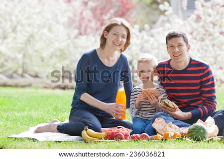happy smiling family of three having picnic in the beautiful park in spring time with blooming trees in the background - stock photo