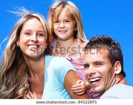 Happy smiling family outdoors. Mother father and daughter. - stock photo