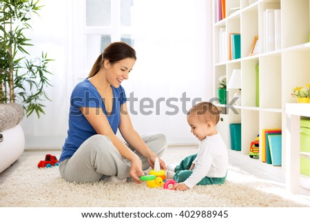 Happy smiling family playing with toys on floor - stock photo