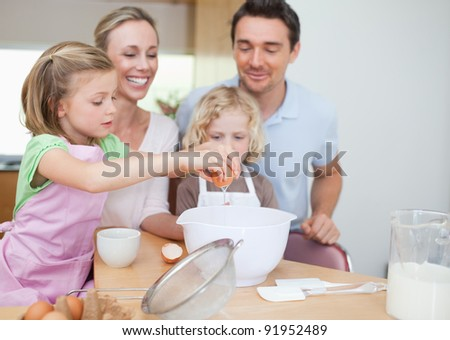 Happy smiling family preparing dough together - stock photo