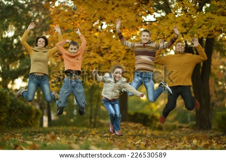 Happy smiling family relaxing in autumn forest - stock photo
