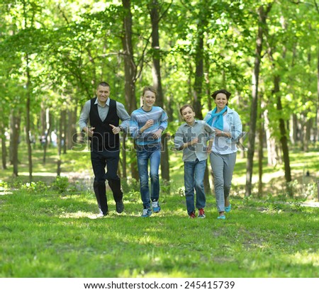 Happy smiling family run in forest - stock photo