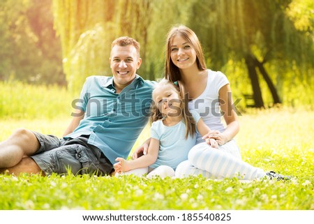 Happy smiling family sitting on the grass in the park and looking at the camera.