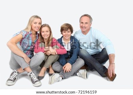 Happy smiling family sitting on white background - stock photo