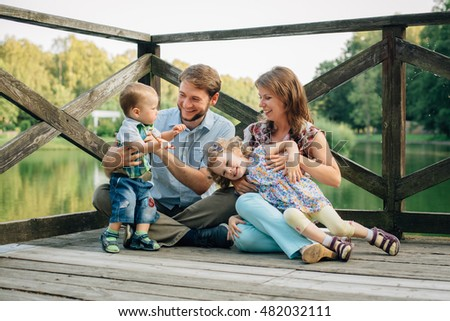 Happy smiling Family Sitting On Wooden Jetty having fun and playing. Parents with cute kids outdoors