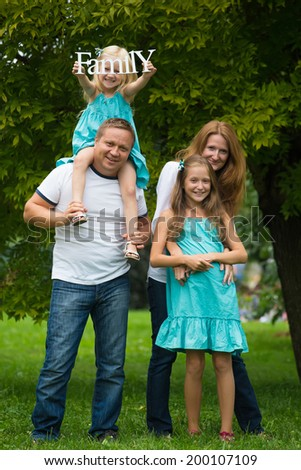 happy smiling family standing at the park  - stock photo