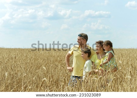 Happy smiling family standing on wheat field - stock photo