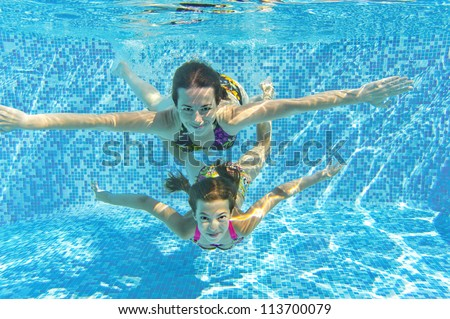 Happy smiling family underwater in swimming pool. Mother and child swim and having fun. Kids sport on family summer vacation. Active healthy holiday - stock photo