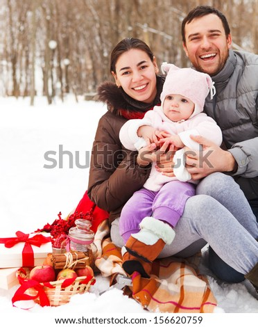 Happy smiling family with at the winter picnic outdoors - stock photo