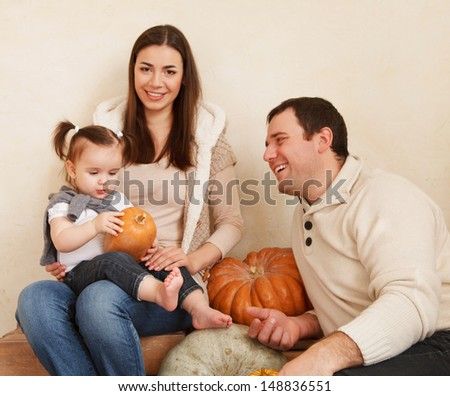 Happy smiling family with autumn pumpkins indoor