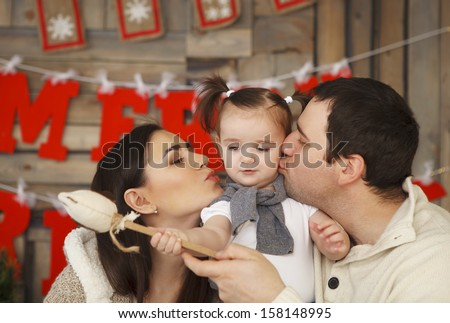 Happy smiling family with one year daughter near the Christmas background