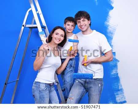Happy smiling family with paintbrushes doing renovation - indoors - stock photo