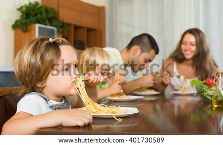 Happy smiling family with playful kids eating with spaghetti at table. Focus on girl