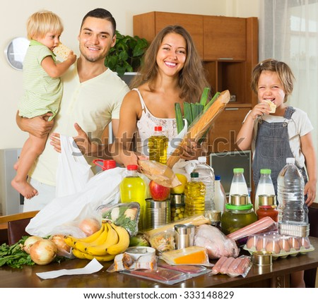Happy smiling family with two little kids came back from supermarket