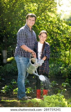 Happy smiling father and daughter watering garden bed at hot sunny day