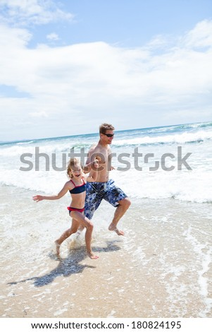 Happy smiling father and young daughter holding hands and running along beach in shallow water - stock photo