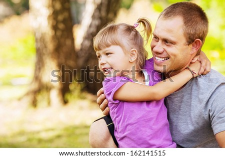Happy smiling father with her daugter  on hands - stock photo