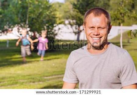 Happy smiling father with his running children - stock photo