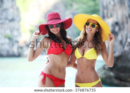 Happy smiling female friends in bikini and sunhats on vacation - stock photo