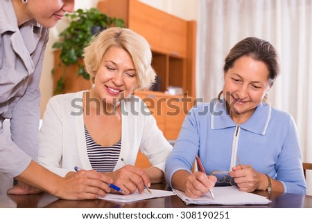 Happy smiling female pensioners signing documents with public notary