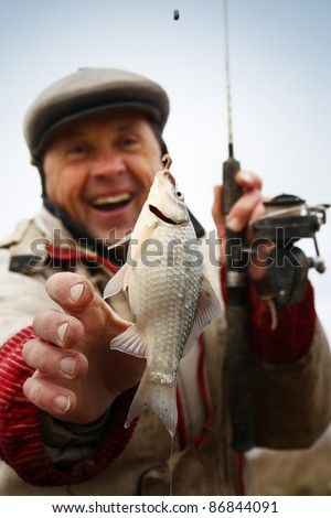 Happy smiling fisherman with fresh caught crucian (Carassius of family Cyprinidae) on clear sky background - stock photo