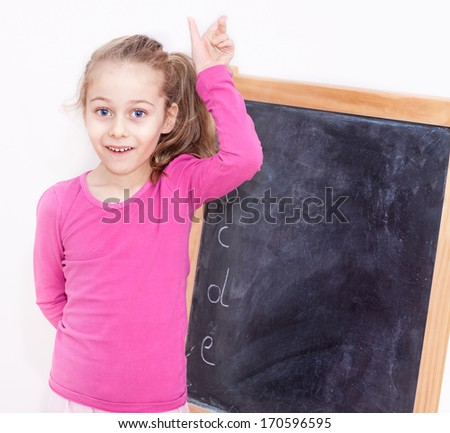 Happy smiling five years old caucasian blond child girl in front of blackboard on white background - education - stock photo