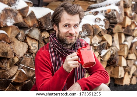 Happy smiling forty years old caucasian man drinking hot tea outdoor in front of stacked chopped firewood - winter countryside landscape - stock photo