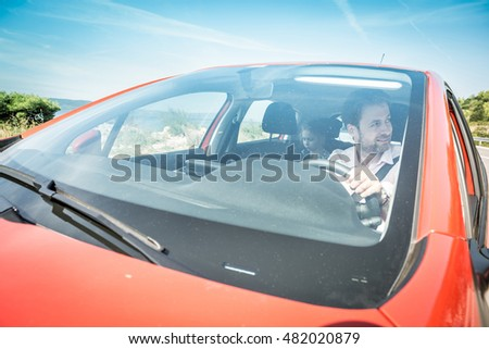 Happy smiling forty years old caucasian man driving a car during holiday. Sunny summer day and beautiful landscape as background.