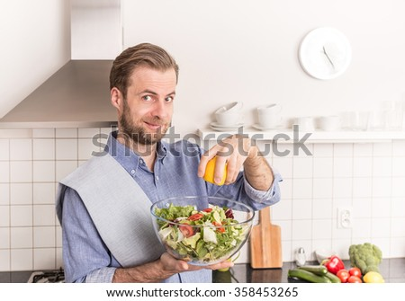 Happy smiling forty years old caucasian man making fresh vegetable salad in the kitchen (squeezing lemon juice for dressing). Healthy food and diet concept. - stock photo