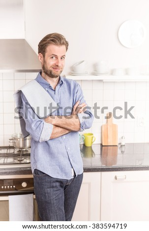 Happy smiling forty years old caucasian man or chef  standing in the bright kitchen