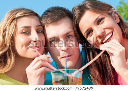 Happy smiling friends drinking with plastic straw a cold drink in summer - stock photo
