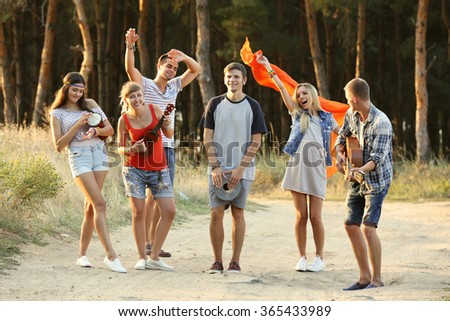 Happy smiling friends playing musical instruments in the forest outdoors - stock photo