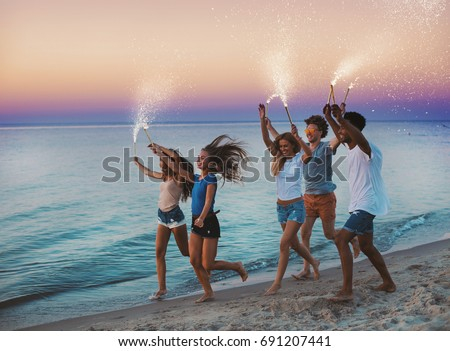 Happy smiling friends running at the beach with sparkling candles