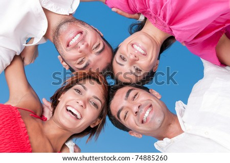 Happy smiling friends with their heads together looking at camera in a sunny day - stock photo