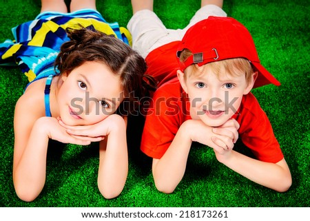 Happy smiling girl and boy in bright summer clothes lying on a grass. Children. - stock photo