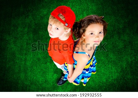 Happy smiling girl and boy in bright summer clothes standing on a grass. Children. - stock photo