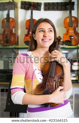 Happy smiling girl choosing full size violin in music shop