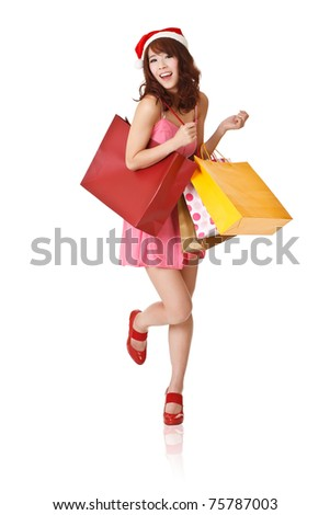 Happy smiling girl holding shopping bags and wearing Christmas hat, full length portrait isolated on white background. - stock photo