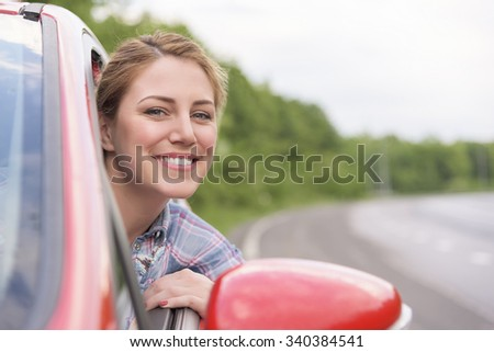 Happy smiling girl in a red car. Travel concept. - stock photo
