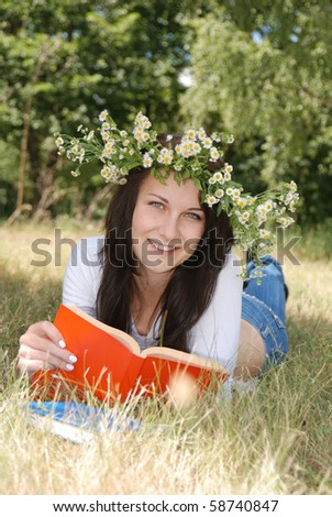 Happy smiling girl in garland reading book outside