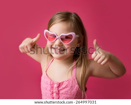 Happy smiling girl in heart shaped pink glasses giving thumbs up; success or achievement - stock photo