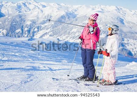 Happy smiling girl in ski goggles and a helmet with his mother, Zellertal, Austria - stock photo