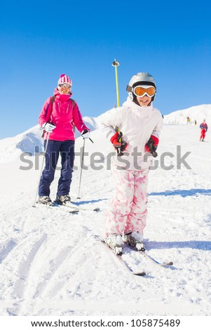 Happy smiling girl in ski goggles and a helmet with his mother, Zellertal, Austria. Vertical view - stock photo