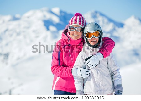 Happy smiling girl in ski goggles and with her mother, Zellertal, Austria. Focus on the girl - stock photo