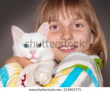 Happy smiling girl is hugging a white kitten. - stock photo