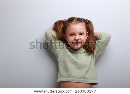 Happy smiling girl looking and showing tongue on blue background with empty copy space. Fun lifestyle - stock photo
