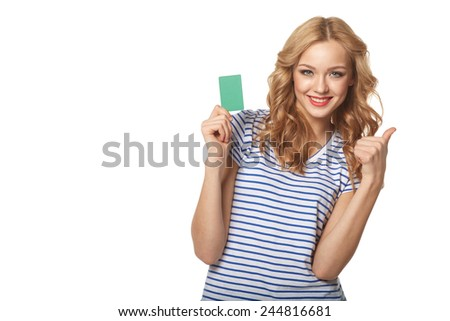 Happy smiling girl showing blank credit card and gesturing thumb up, on white background - stock photo